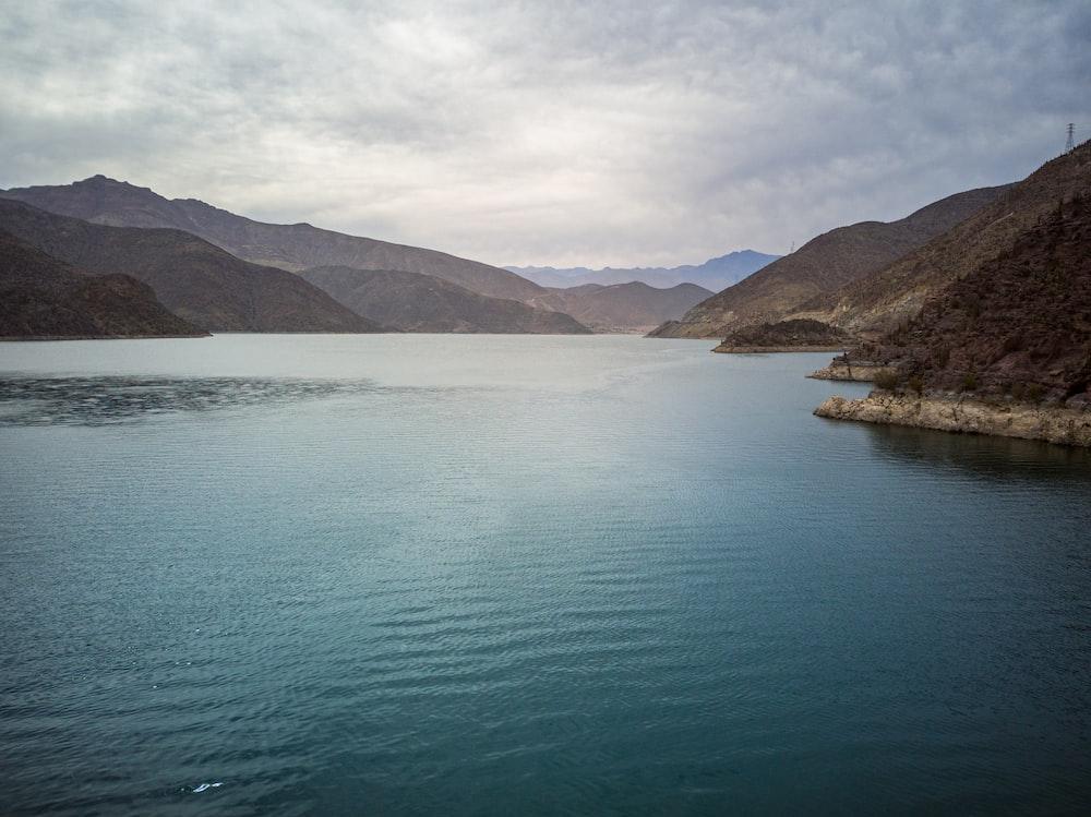 green lake near mountain during daytime