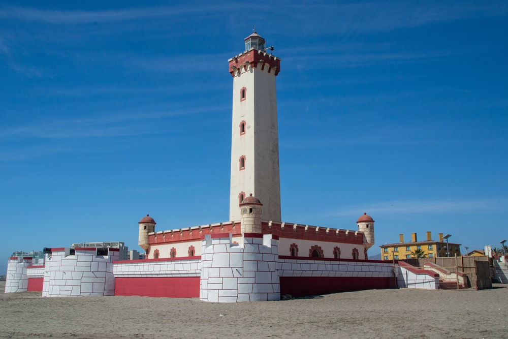 white and brown concrete lighthouse under blue sky during daytime