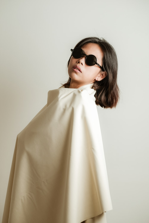 woman in white coat wearing black sunglasses