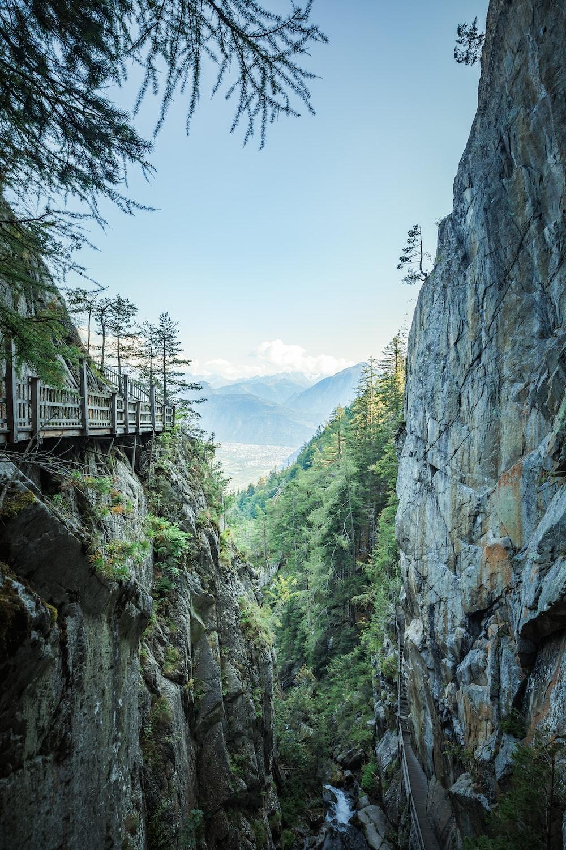 gray concrete bridge on rocky mountain during daytime