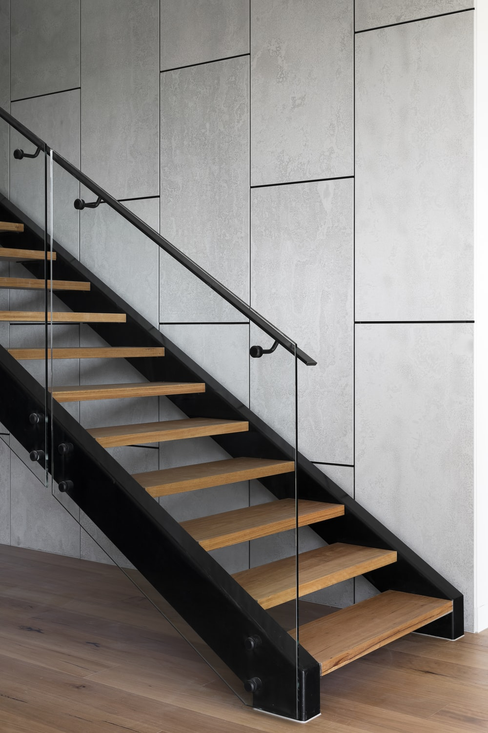 brown wooden staircase with stainless steel railings