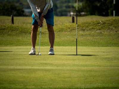 man in white shirt and blue shorts playing golf during daytime