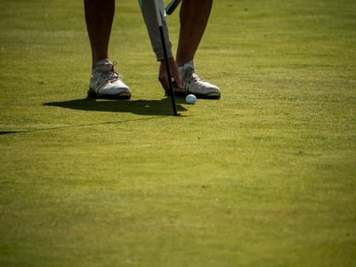 person in white nike shoes playing golf