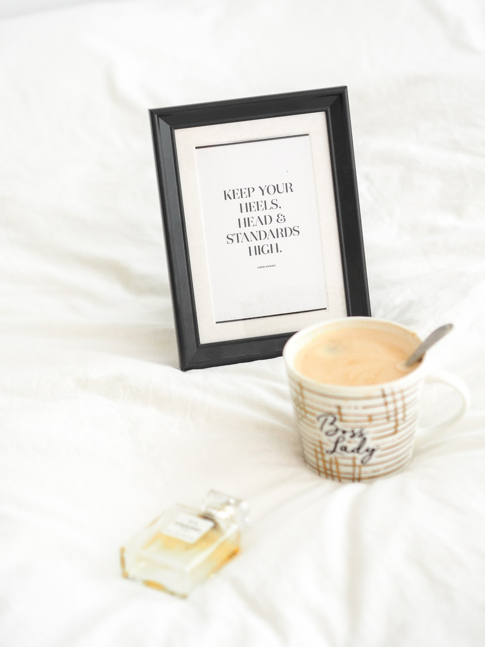 black wooden photo frame beside white and brown ceramic mug