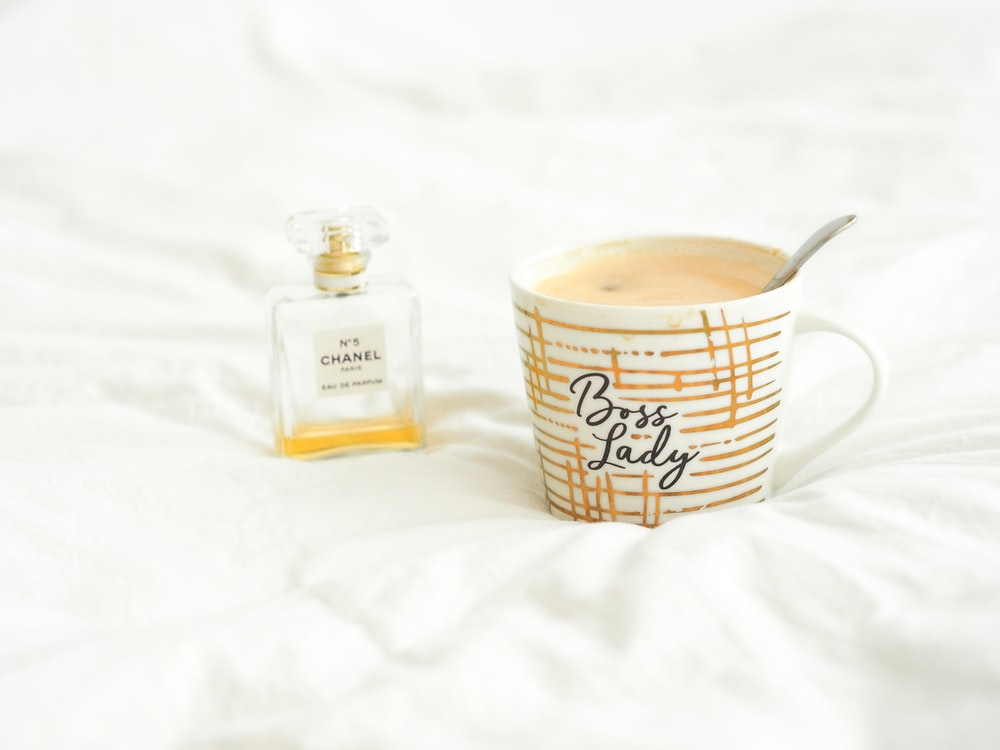 white and brown ceramic mug beside glass bottle