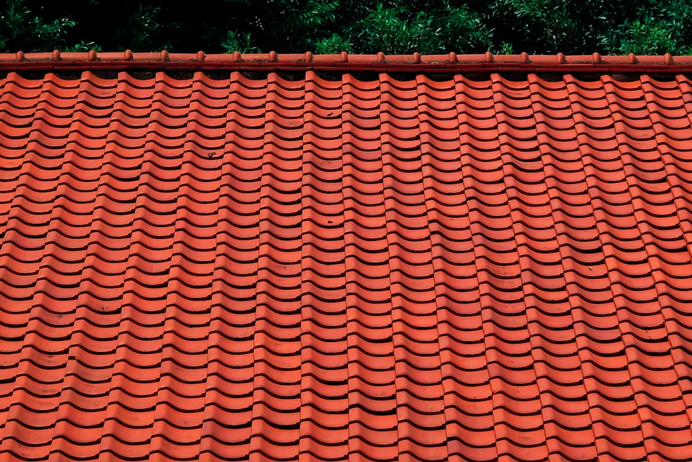 brown roof tiles near green trees during daytime