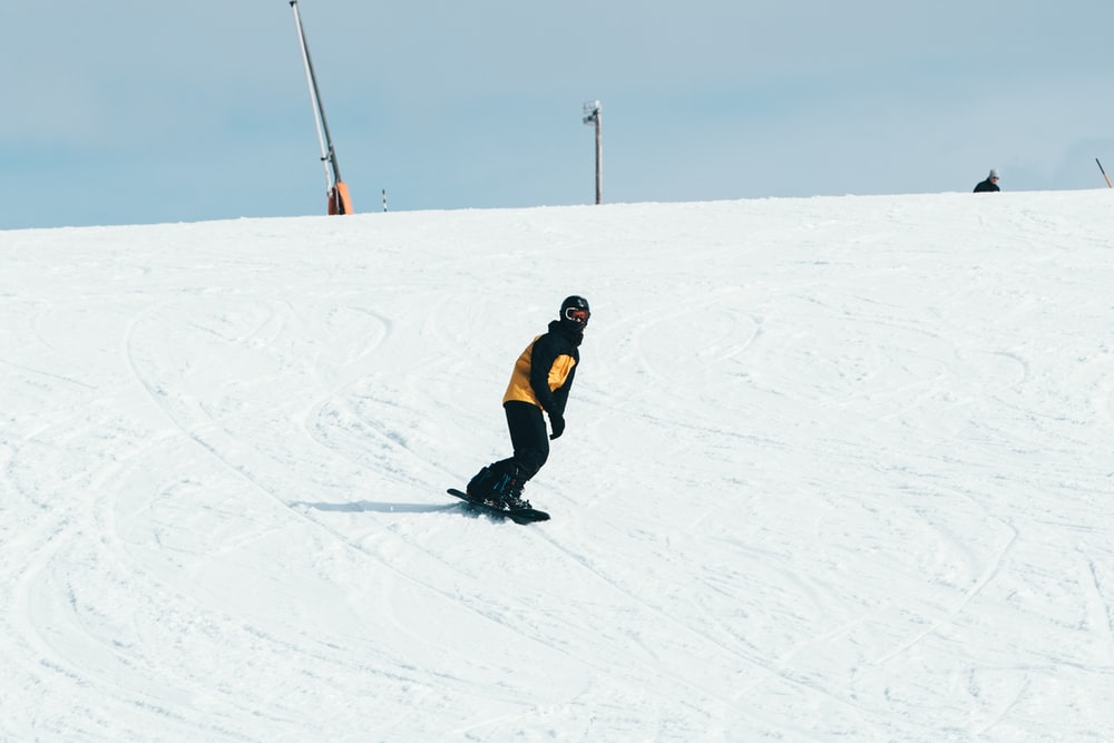 man in black jacket and black pants walking on snow covered ground during daytime