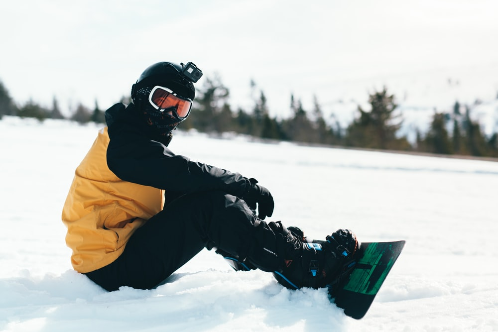 person in yellow jacket and black pants riding on snowboard