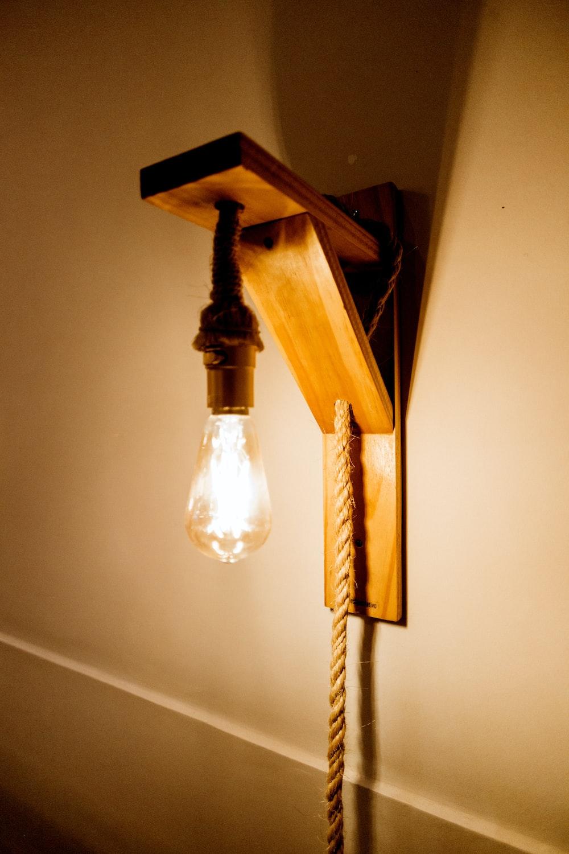 white pendant lamp turned on near white wall