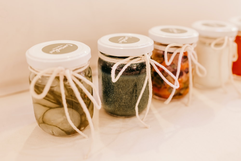 two white and clear glass jars