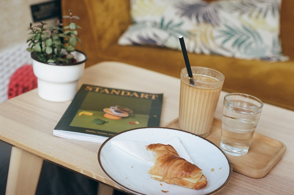 bread on white ceramic plate beside drinking glass