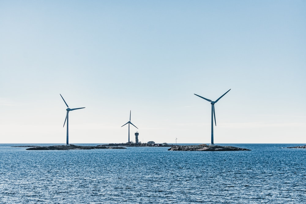 wind turbines on the sea shore during daytime
