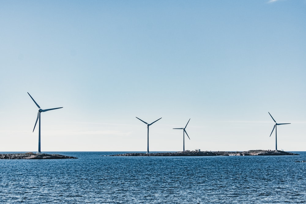 wind turbines on blue sea under blue sky during daytime