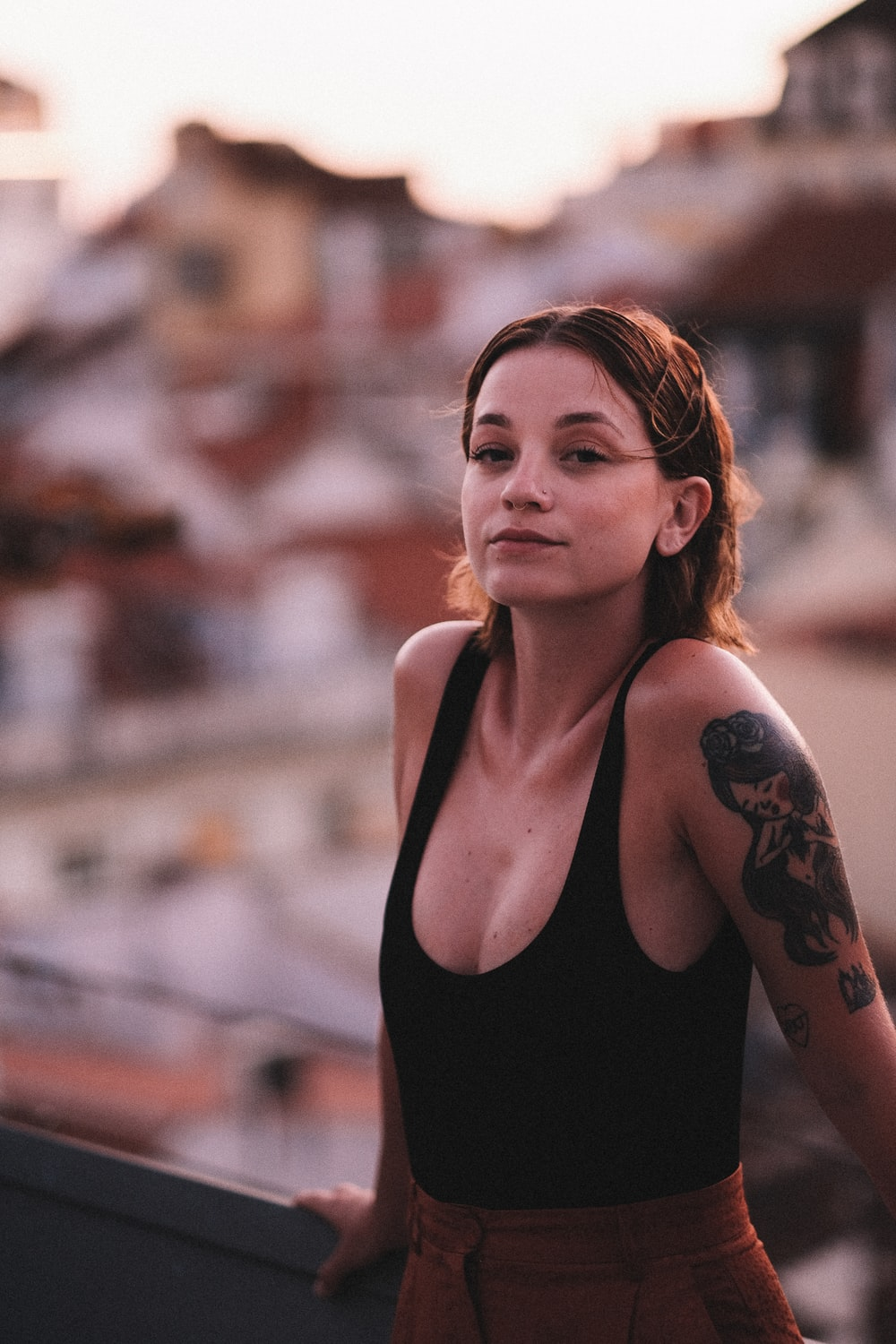 woman in black tank top with black floral tattoo on her left shoulder