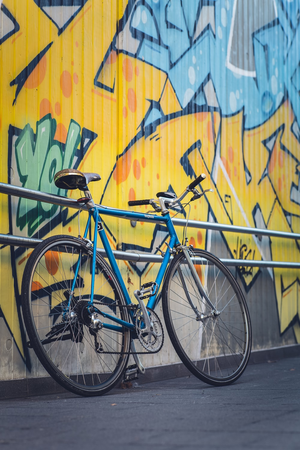 blue city bike beside yellow blue and green wall
