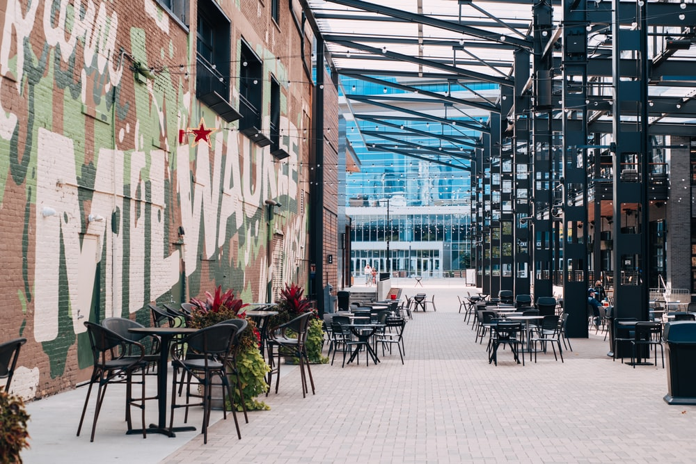 black metal chairs and tables outside building during daytime