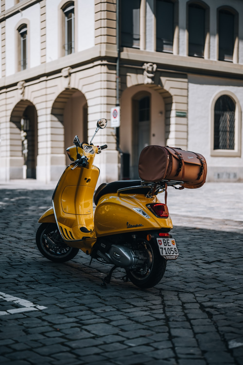 yellow and black motor scooter parked on gray concrete pavement during daytime