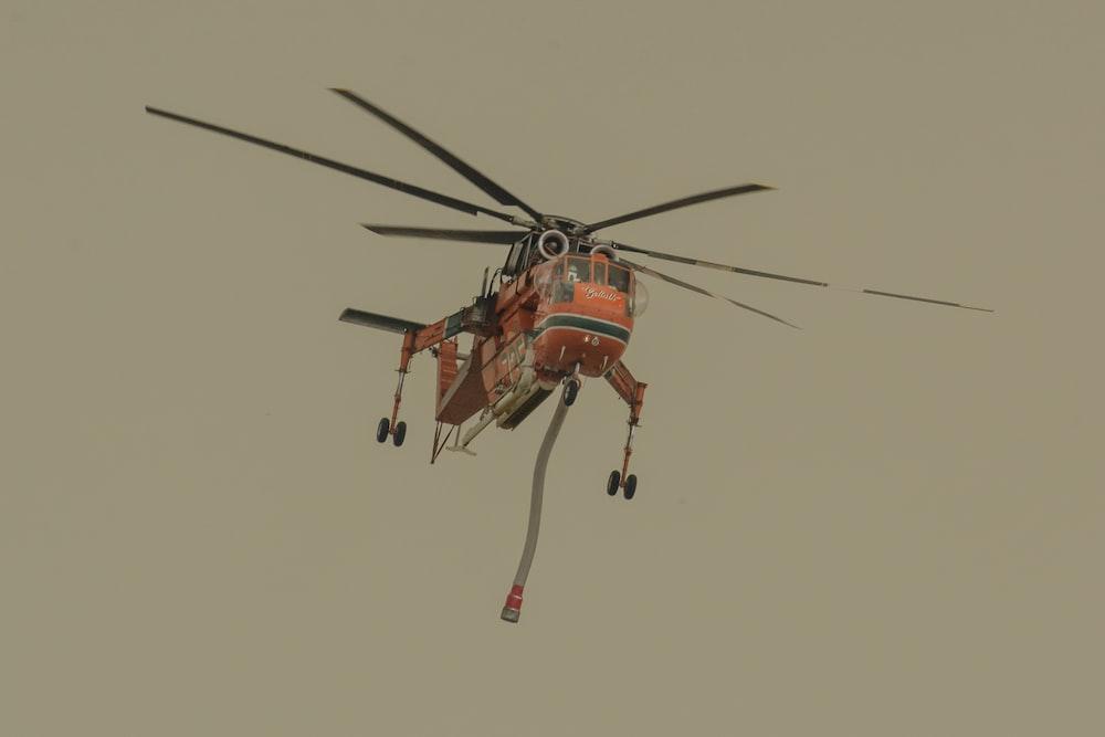 orange and black helicopter flying