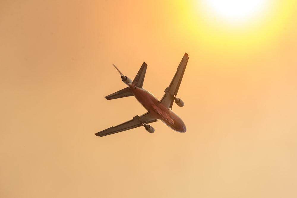 white airplane flying during daytime