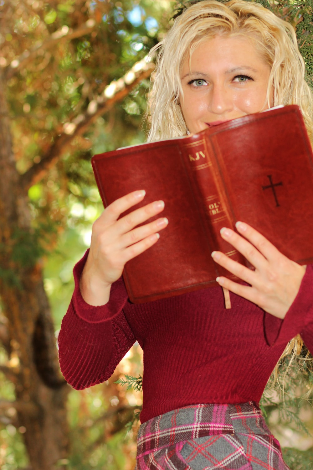 woman in red long sleeve shirt holding red book