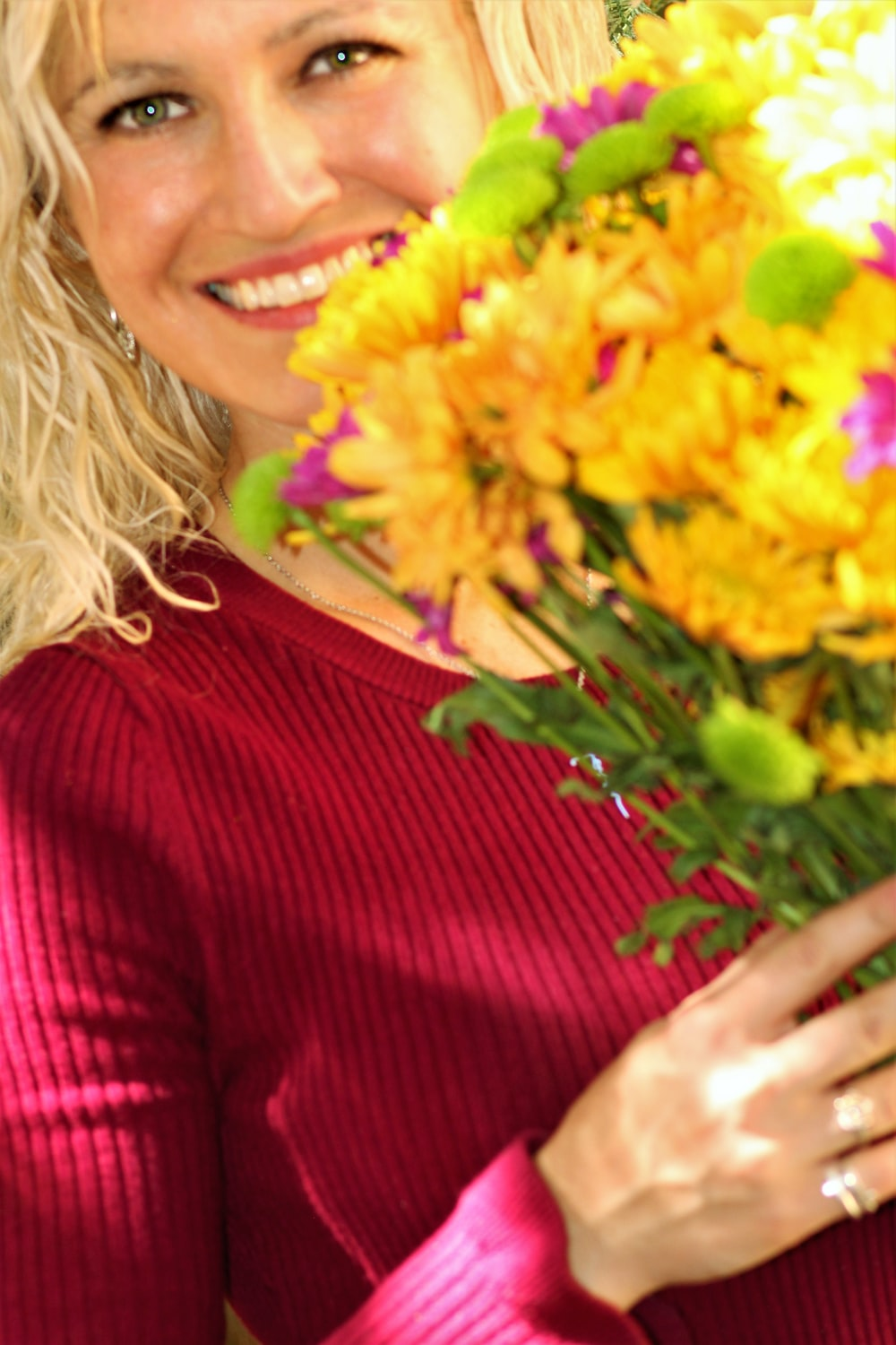 woman in red sweater holding yellow flowers