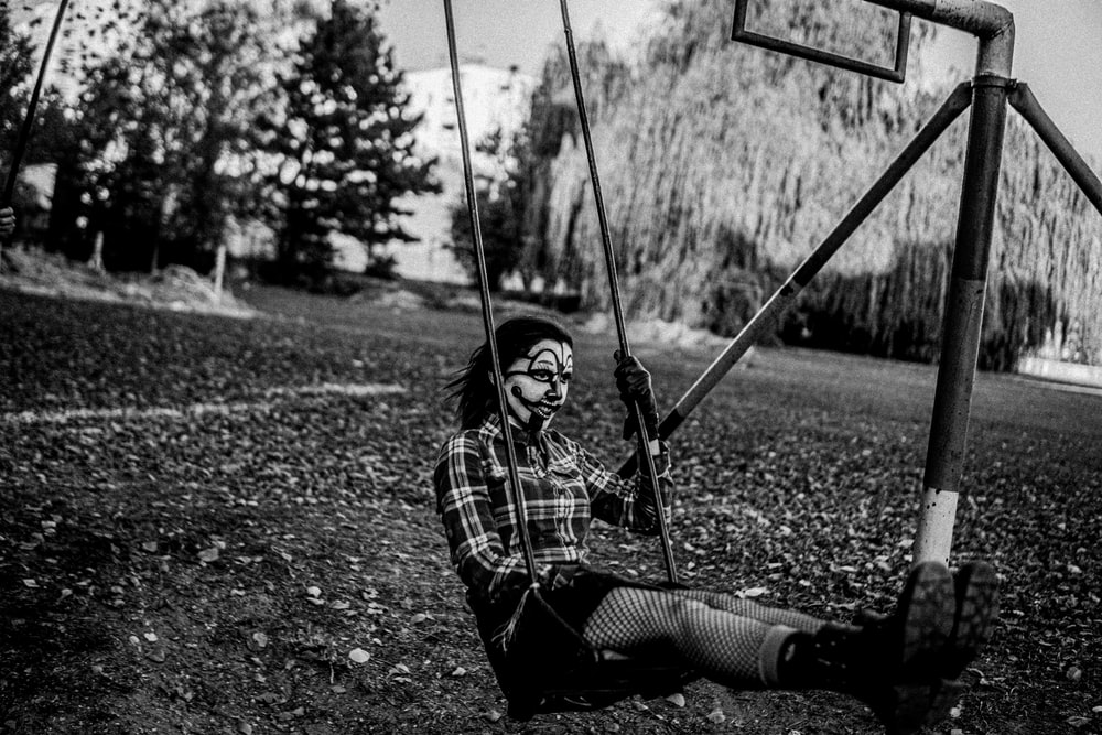 grayscale photo of woman sitting on swing