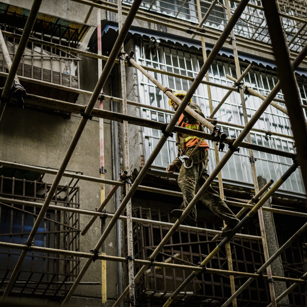 man in brown jacket and black pants climbing on ladder