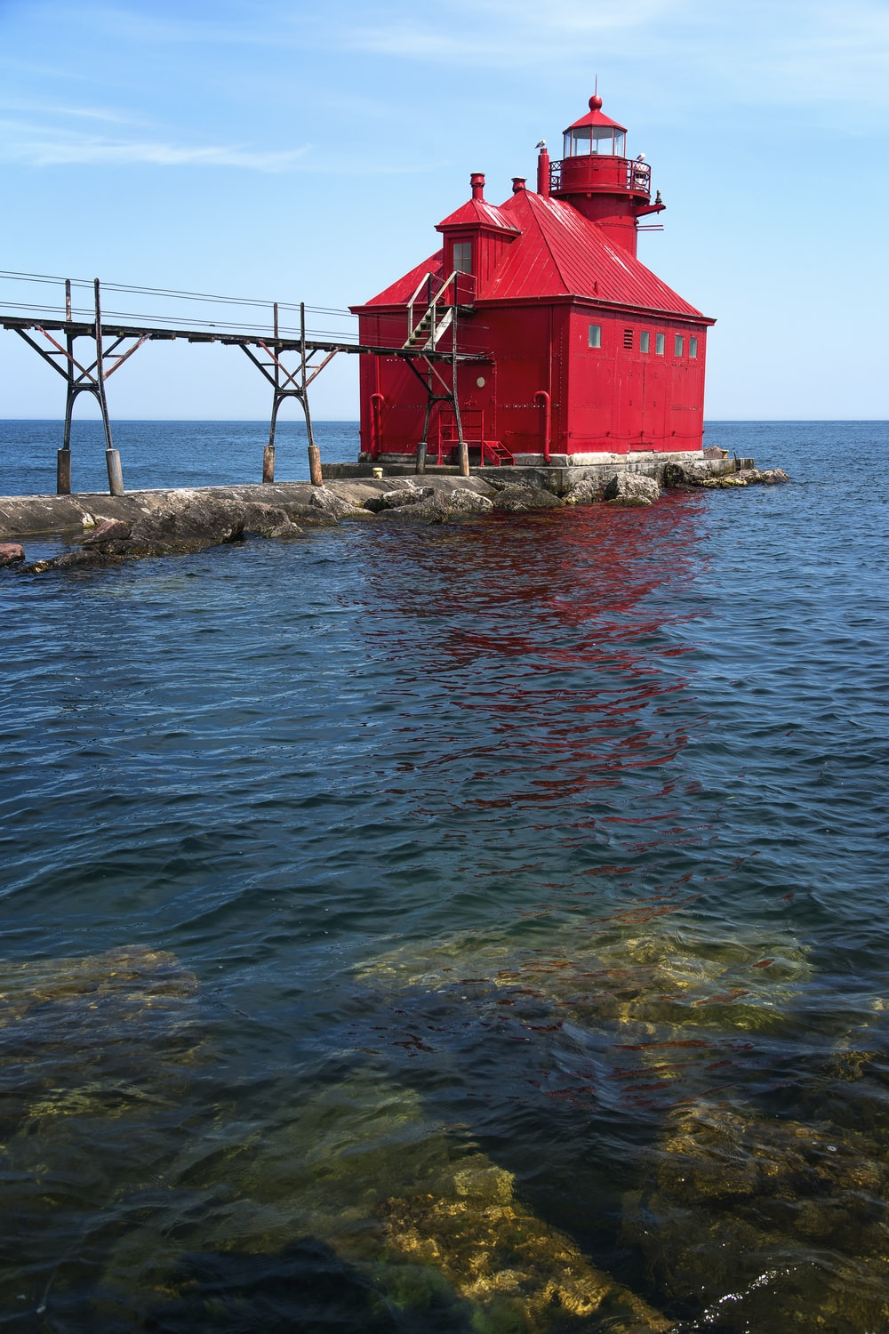 red and white wooden house beside body of water during daytime