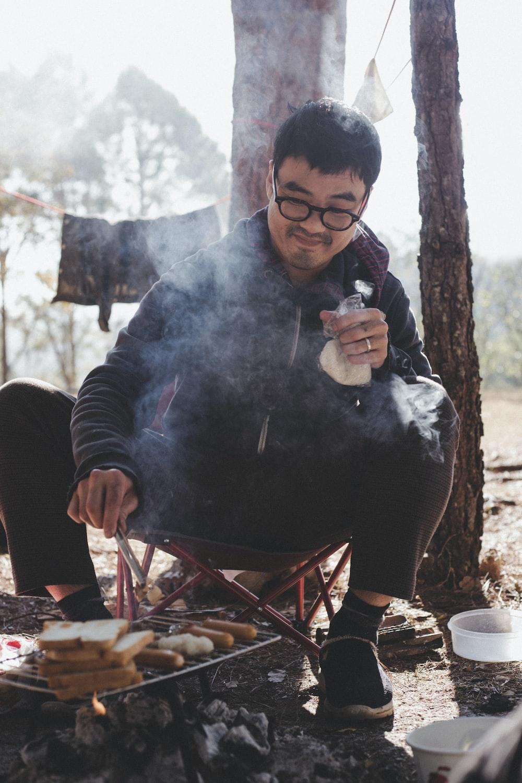 man in black jacket holding white ceramic mug