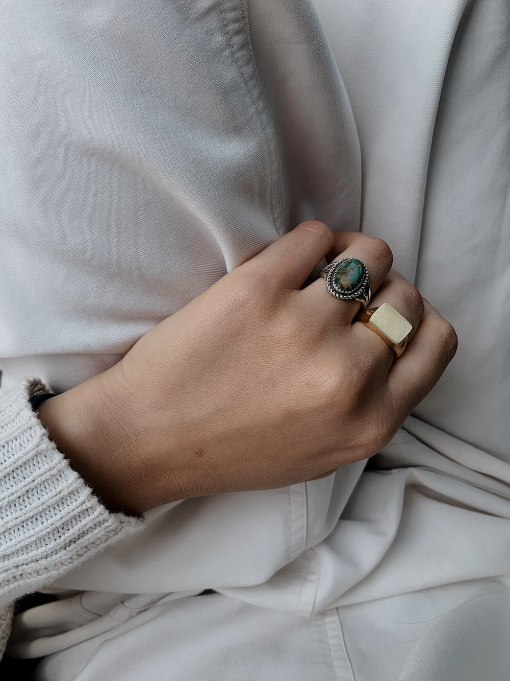 person wearing silver and green ring