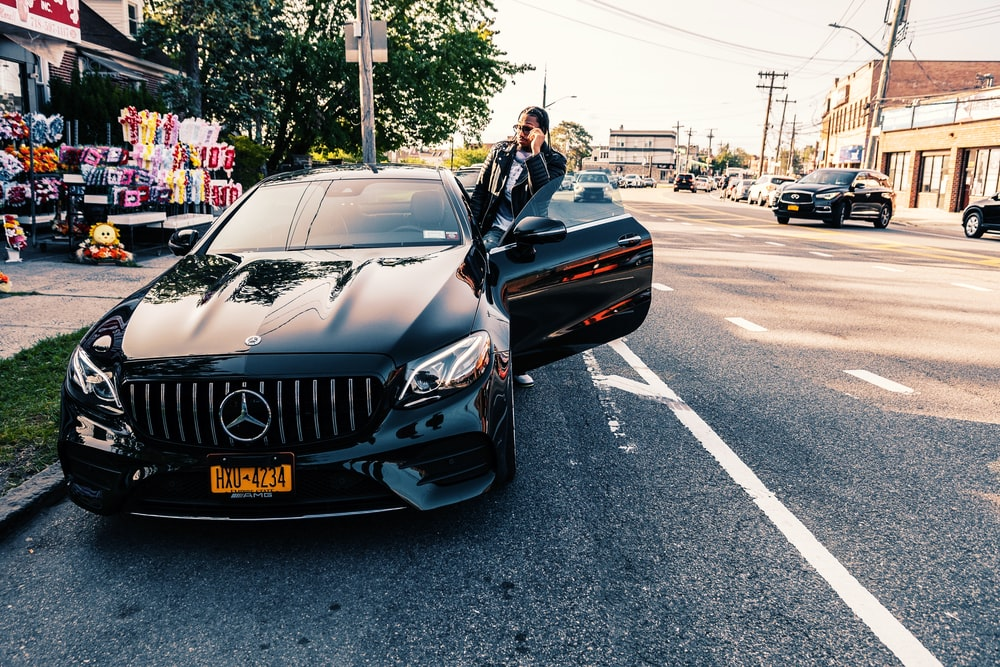 man in black jacket standing beside black bmw car on road during daytime
