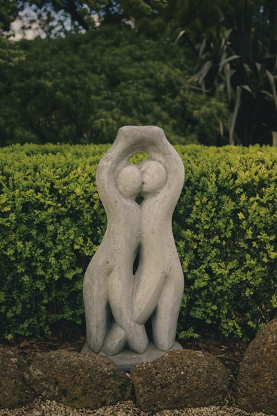 white concrete statue near green trees during daytime