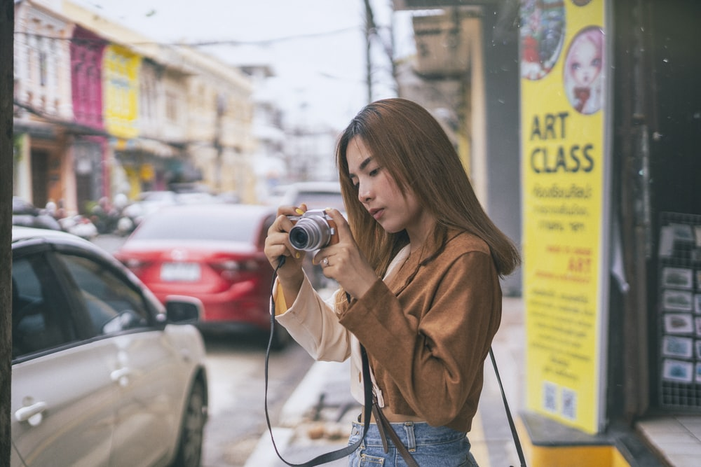 woman in brown coat holding camera