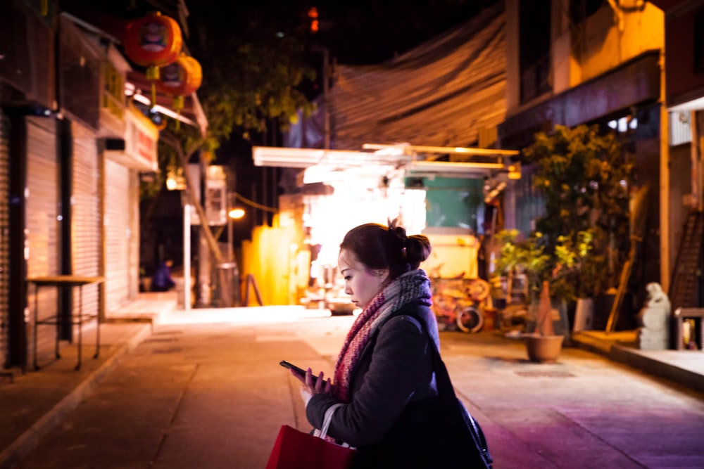 woman in black jacket sitting on red chair during night time