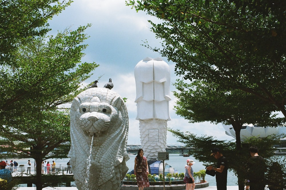 people standing near white animal statue during daytime