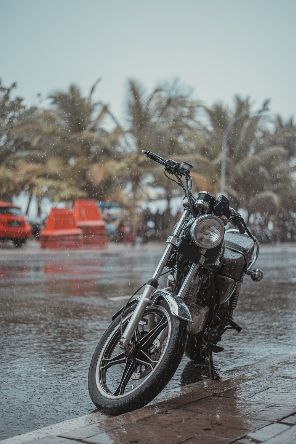 black motorcycle parked beside body of water during daytime