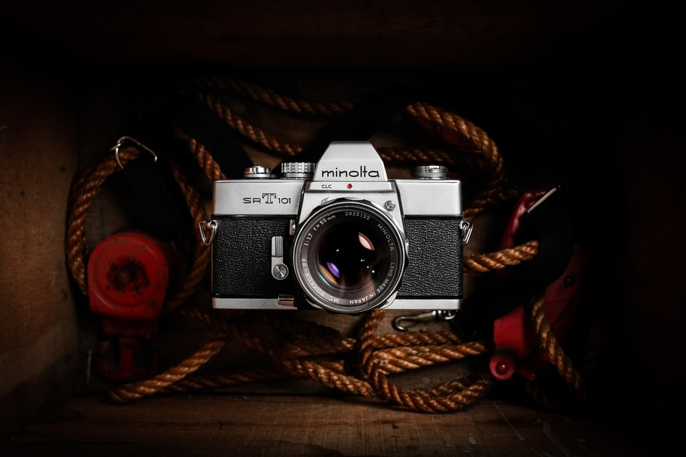 black and silver dslr camera on brown rope