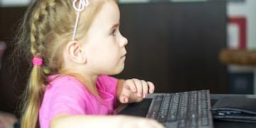 girl in pink shirt using black laptop computer