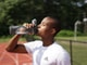 man in white crew neck t-shirt drinking from black sports bottle