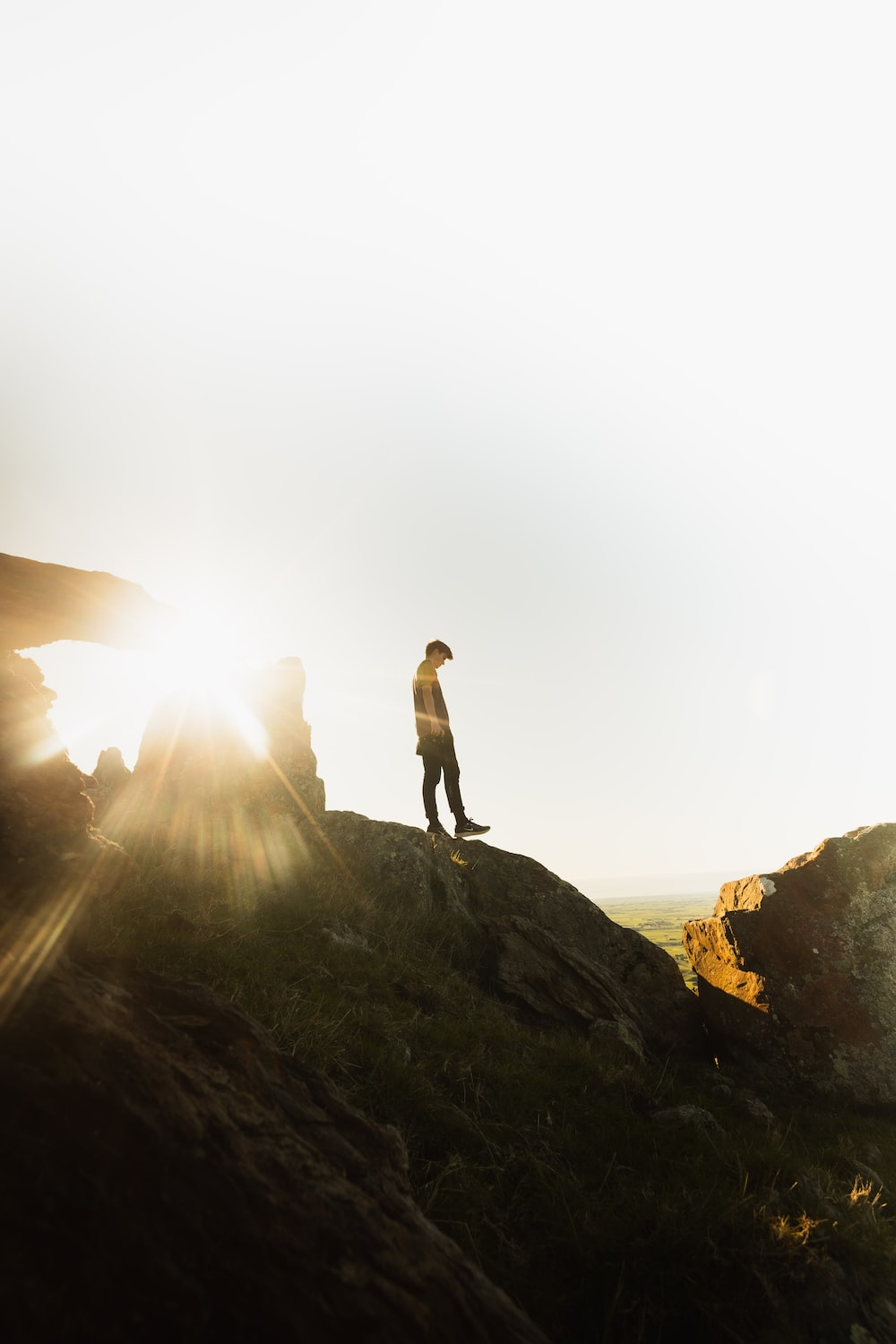 man in white shirt standing on rock formation during daytime