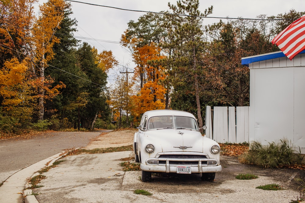 white volkswagen beetle parked beside white wooden fence during daytime