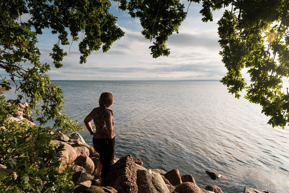woman in black tank top and black pants standing on brown rock near body of water
