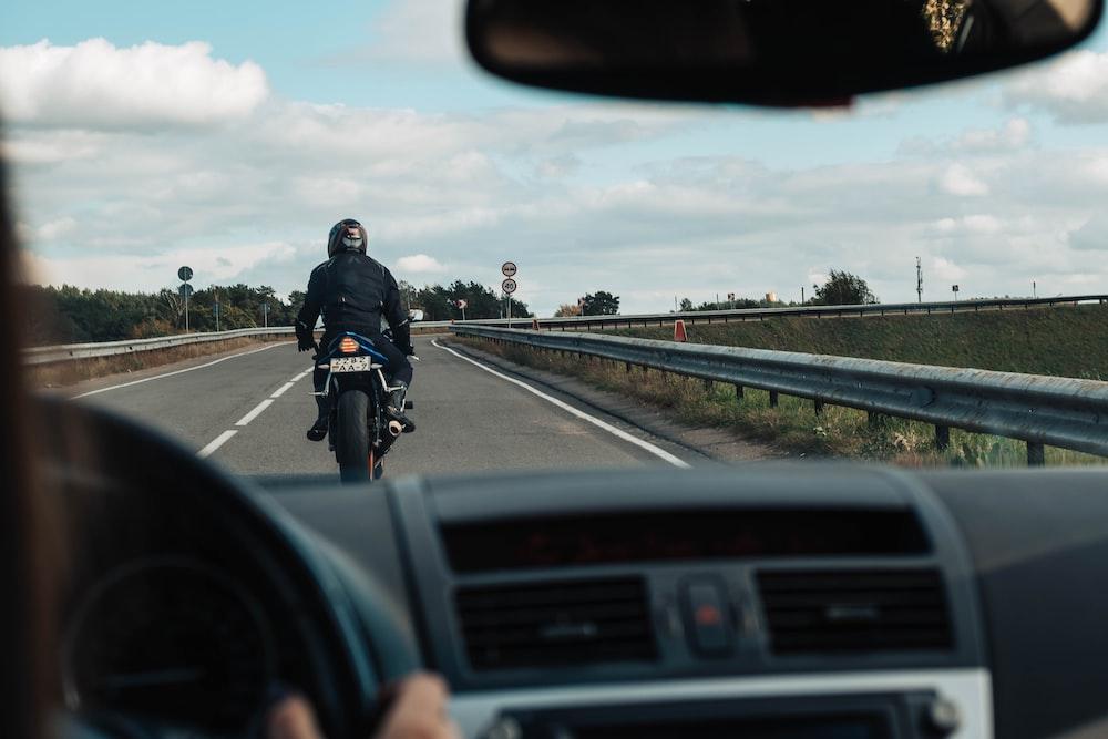 man in black jacket riding motorcycle on road during daytime