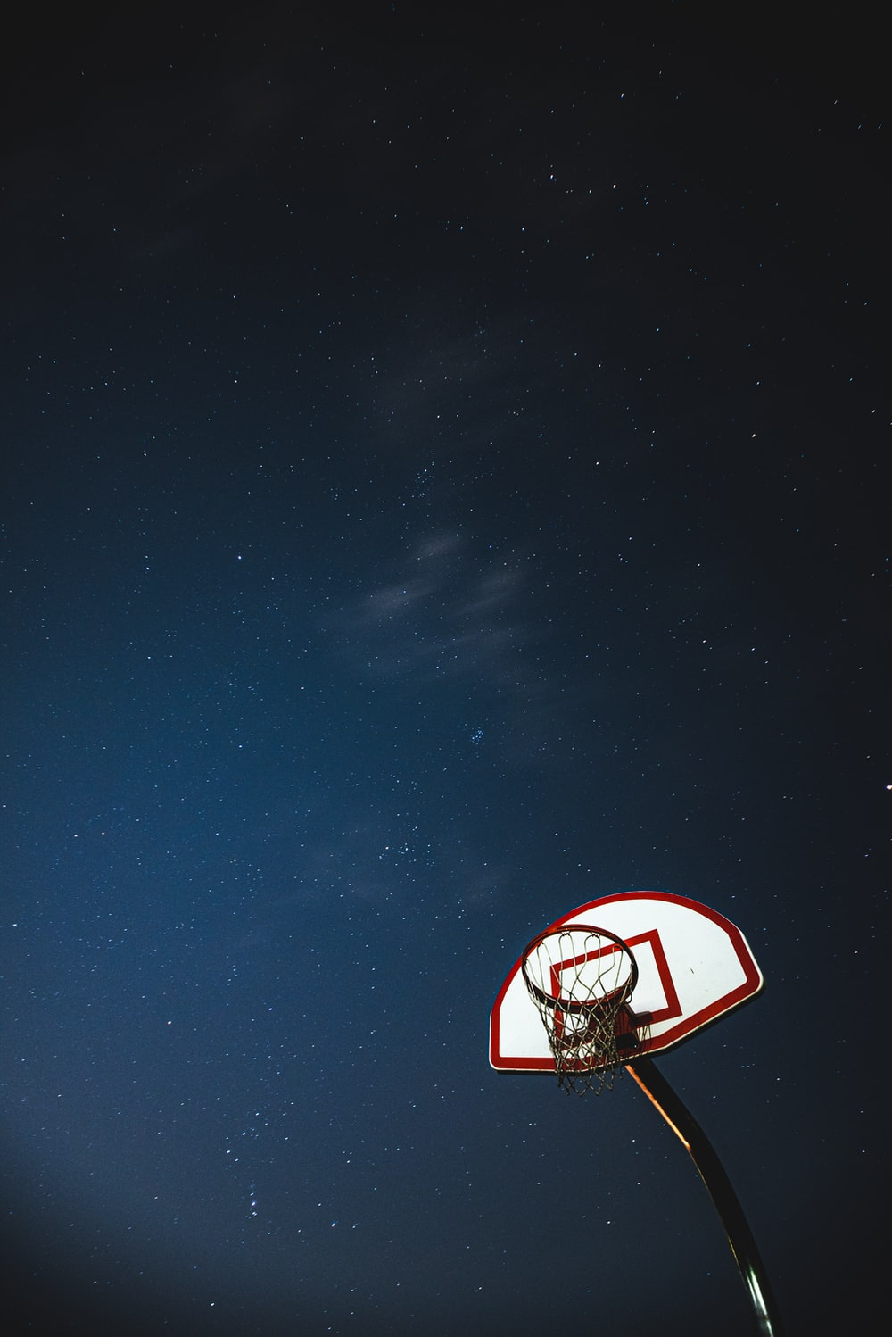 white and red basketball hoop under blue sky