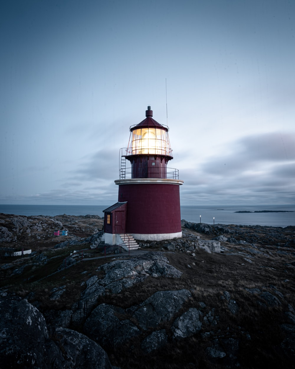 red and white lighthouse on gray rocky mountain under gray cloudy sky
