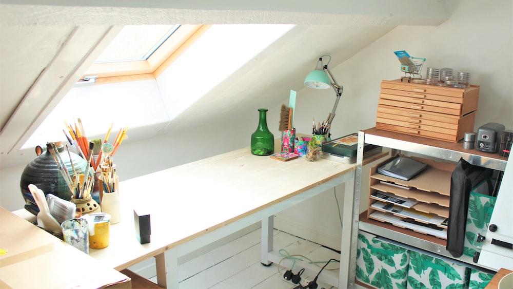green glass bottle on white wooden desk