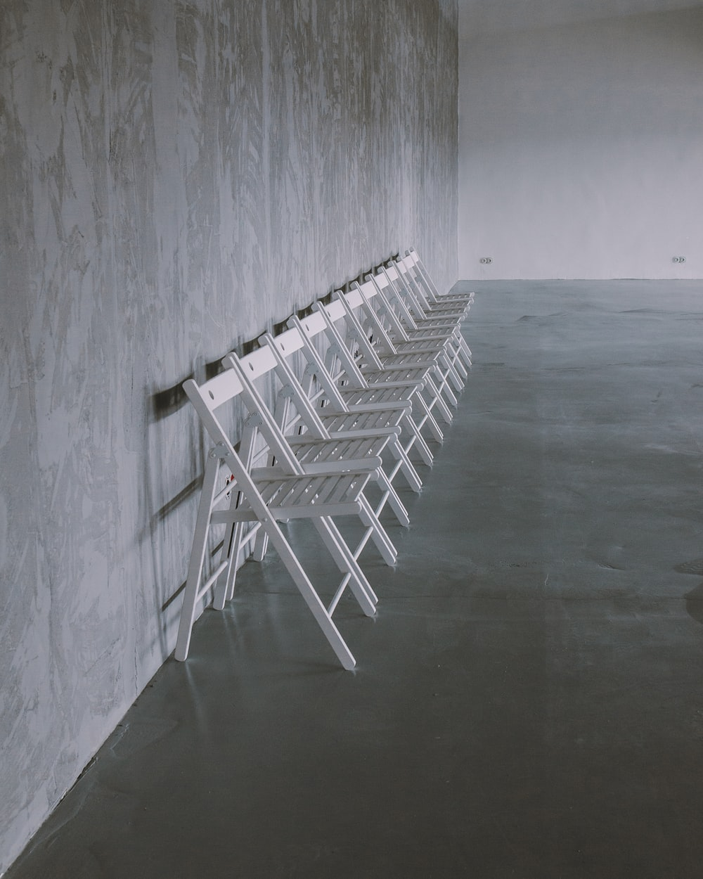 white folding chairs on gray floor