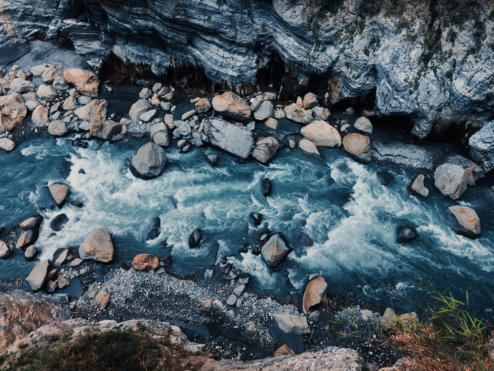 gray and black stone on river