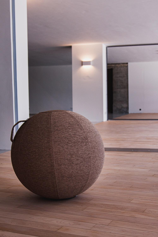 brown round cushion on brown wooden parquet floor