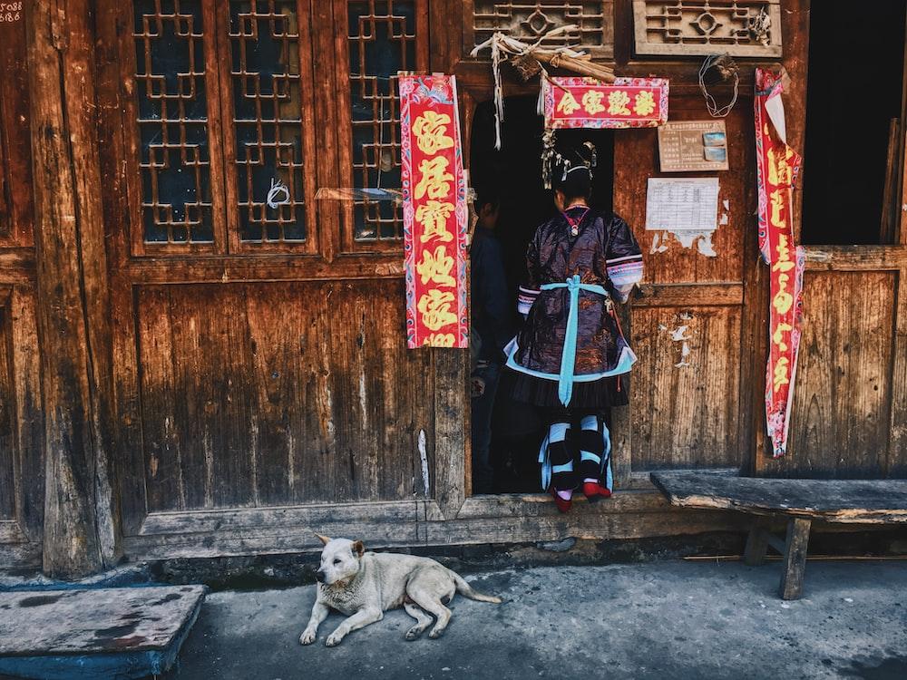 woman in black jacket and blue pants standing beside brown wooden door during daytime